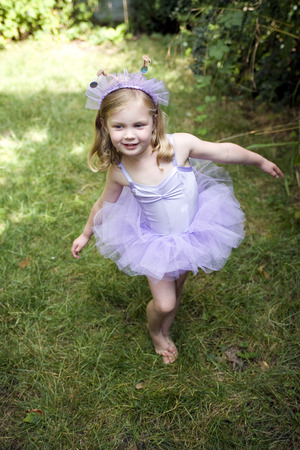 Little girl wearing ballet dress dancing happily photo
