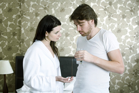 taking a wife: A woman giving the man medication Stock Photo