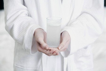 effervescence: Hands holding a glass of effervescence Stock Photo