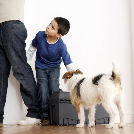 Boy looking at his father while trying to carry toolbox photo