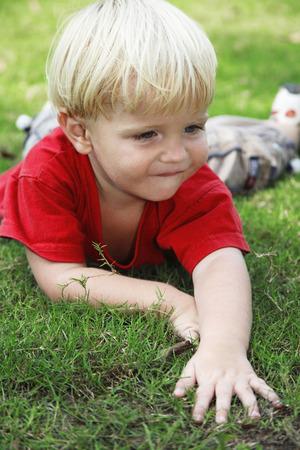 lying forward: Boy lying forward on the field Stock Photo