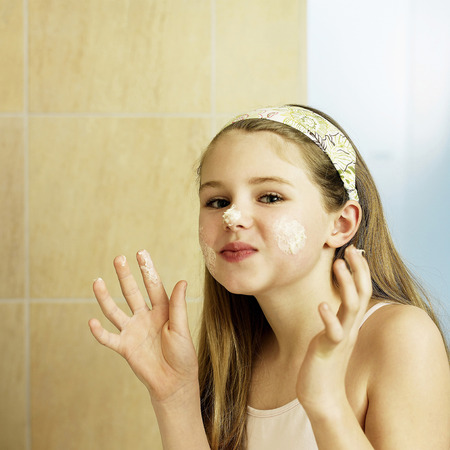 Little girl doing facial in bathroom