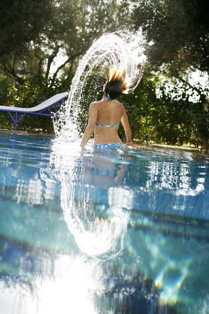 Woman emerging from under the water splashing her hair photo
