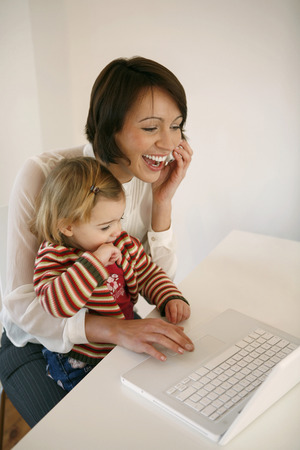 Woman talking on the phone and using laptop while taking care of her daughter photo