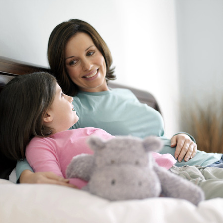 Mother and daughter resting on the bed talking photo