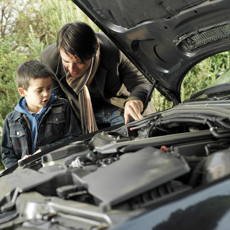 Father and son checking the condition of their car photo