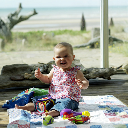 Baby girl sitting on the picnic blanket with her toys photo