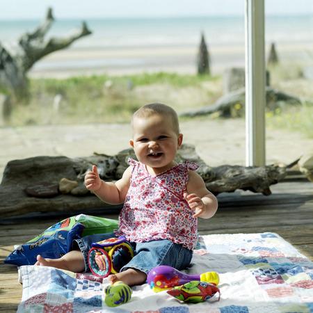 picnic blanket: Ni�a sentada en la manta de picnic con sus juguetes Foto de archivo