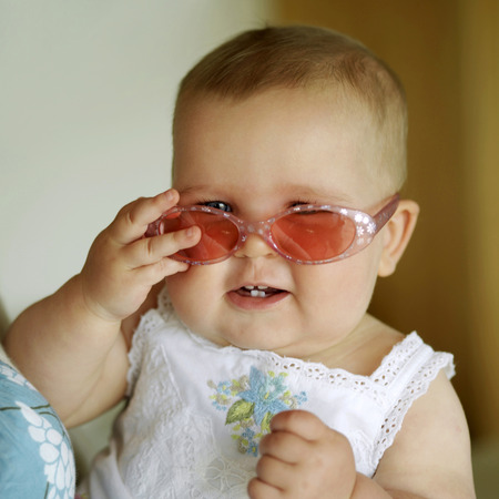 Baby girl smiling while wearing sunglasses photo
