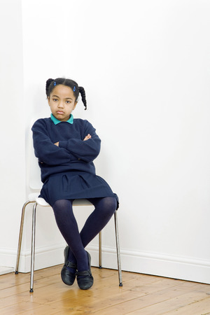 Girl folding her arms while sitting on chair photo