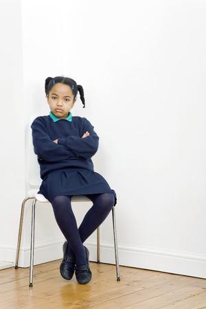Meisje vouwen haar armen zittend op stoel