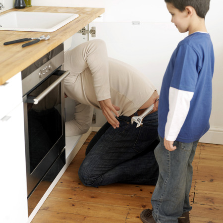 full grown: Boy watching his father fixing the sink