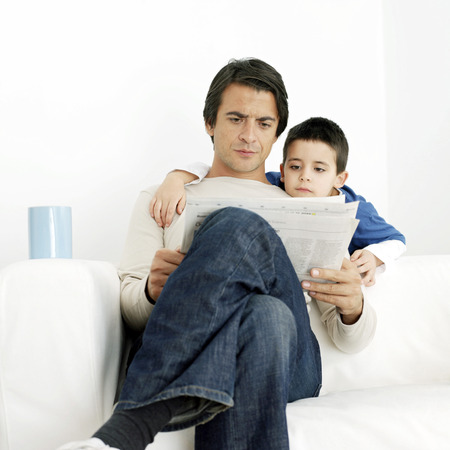 Father and son reading newspaper photo