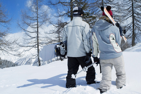 Rear view of couple walking away from camera, holding winter sport equipments photo