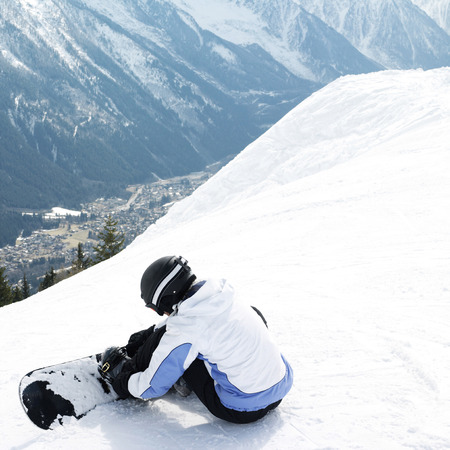 strapping: Female snowboarder strapping board onto feet Stock Photo