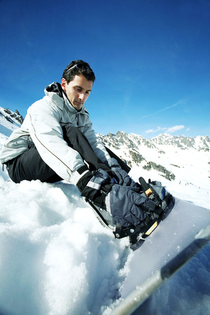 strapping: Male snowboarder strapping board onto feet Stock Photo