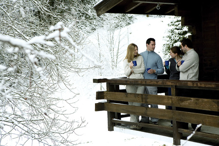 Two couples enjoying hot drinks in their chalet Stock Photo
