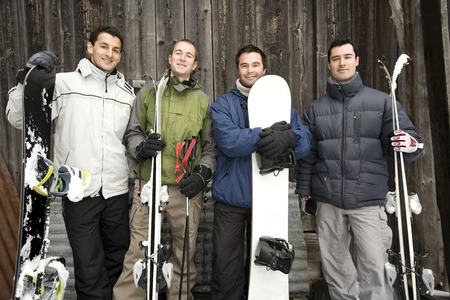 Winter sport players with their skis and snowboards photo