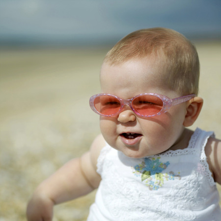 Baby girl with sunglasses sitting on the beach photo