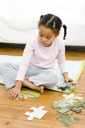 Girl playing with jigsaw puzzle 写真素材