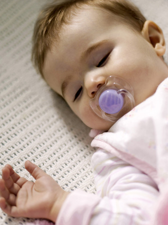Baby girl with pacifier sleeping in the crib photo