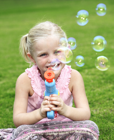 Girl playing with soap bubbles photo