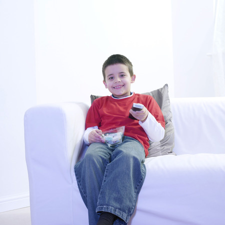 Boy holding a bowl of candies while watching television photo