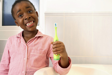 Girl showing her teeth while holding a toothbrush photo