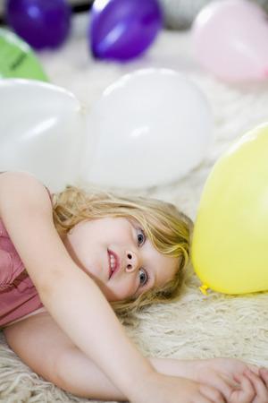 girl lying down: La muchacha se acuesta con globos de colores a su alrededor