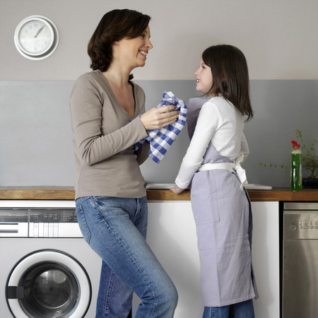 Mother and daughter washing the dishes together photo