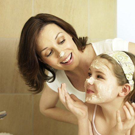 Mother and daughter washing face in the bathroom