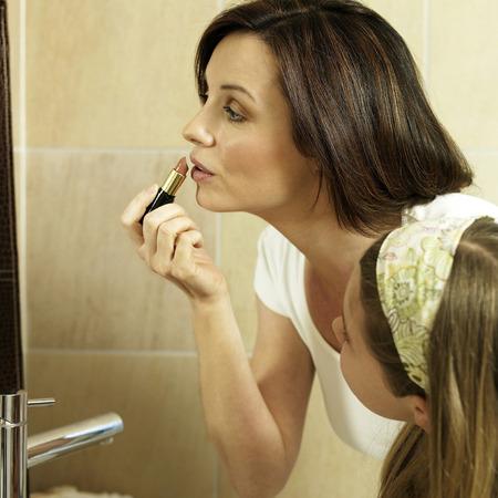 Girl watching her mum applying make-up photo