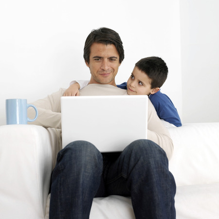 Son watching father using laptop photo