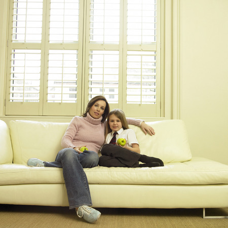 full grown: Mother and daughter sitting on the couch holding green apples Stock Photo