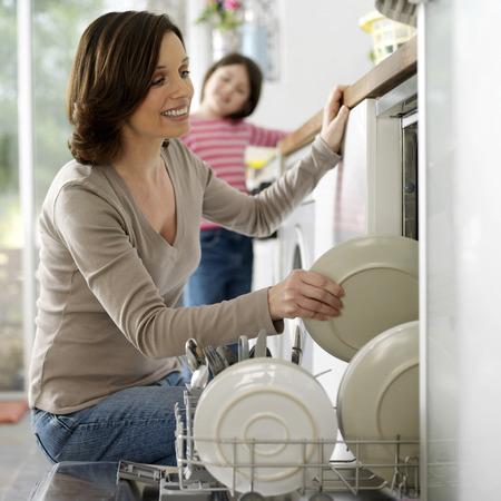 lavavajillas: Chica mirando a su madre manteniendo los platos en el lavavajillas Foto de archivo