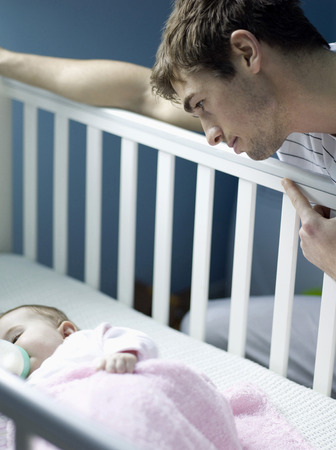 Father watching baby girl sleeping in the crib