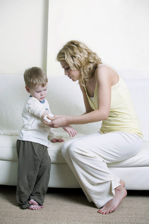 Mother wrapping sons arm with bandage photo