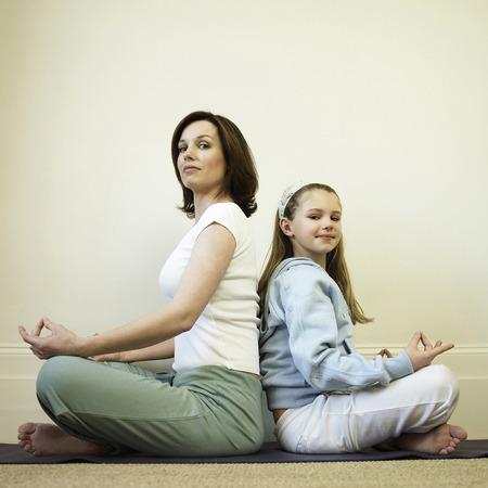 mujer meditando: Madre e hija a practicar yoga Foto de archivo