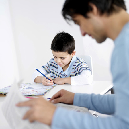Father reading newspaper with son doing homework in the background photo