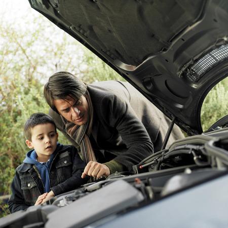 problemas familiares: Padre e hijo comprobar el estado de su coche Foto de archivo