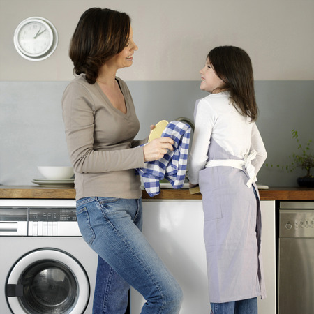 Mother and daughter washing the dishes together