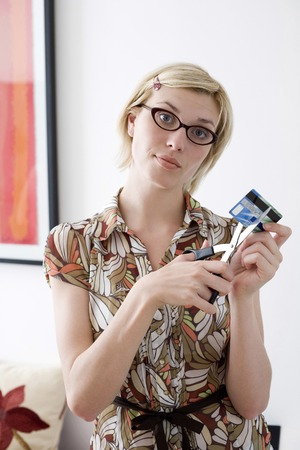 Woman cutting her credit card with scissors photo
