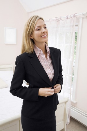 buttoning: Woman smiling while buttoning her blazer Stock Photo