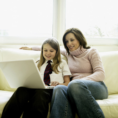 Mother and daughter sitting on the couch using laptop photo
