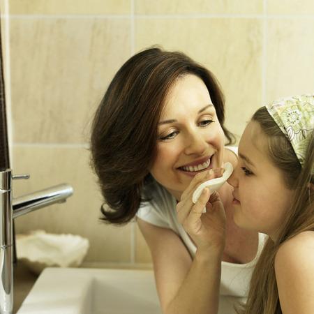 pulizia viso: Madre pulizia del viso della figlia con un cotone viso