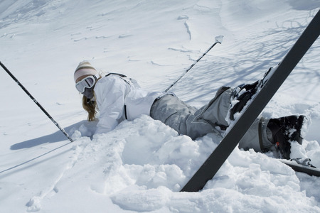 Woman fall down while skiing