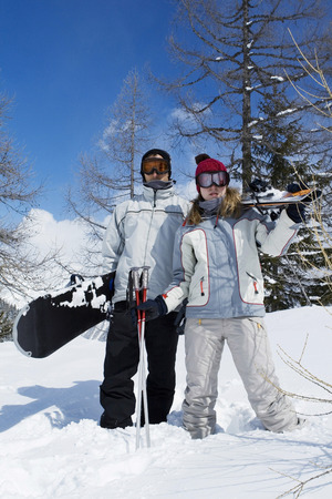 Couple holding winter sport equipments, looking at camera photo