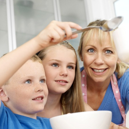 Boy baking, woman and girl watching photo