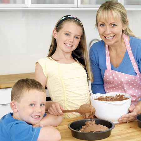 Woman and girl baking in the kitchen, boy smiling at the camera photo