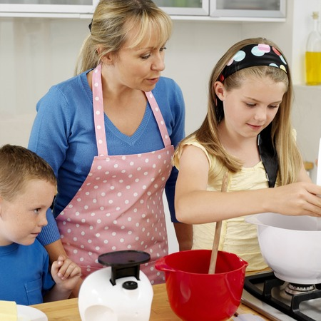 Girl pouring flour into mixing bowl, woman and boy watching photo